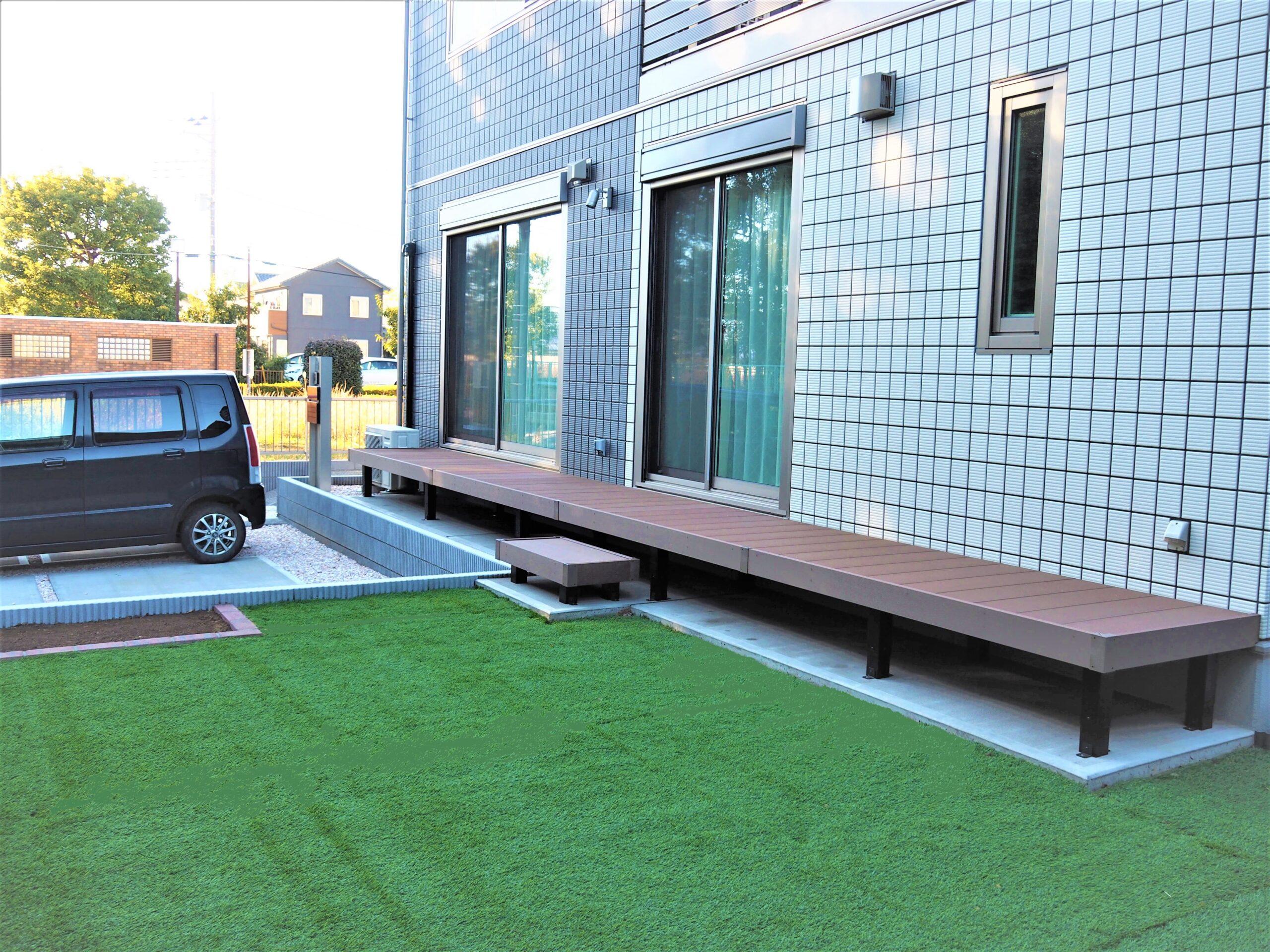 【牛久市 E様邸】 広々としたウッドデッキの濡れ縁と、人工芝の庭がシャープな印象の建物と調和したエクステリア